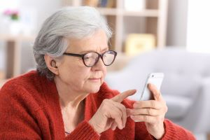 senior looking at smartphone